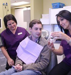 Dental hygienists showing a male dental mouthguard