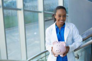 dentist in Burlington smiling and holding pink piggy bank