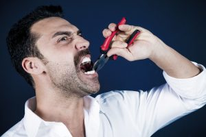 Man pulling his tooth with pliers instead of seeing his Burlington emergency dentist