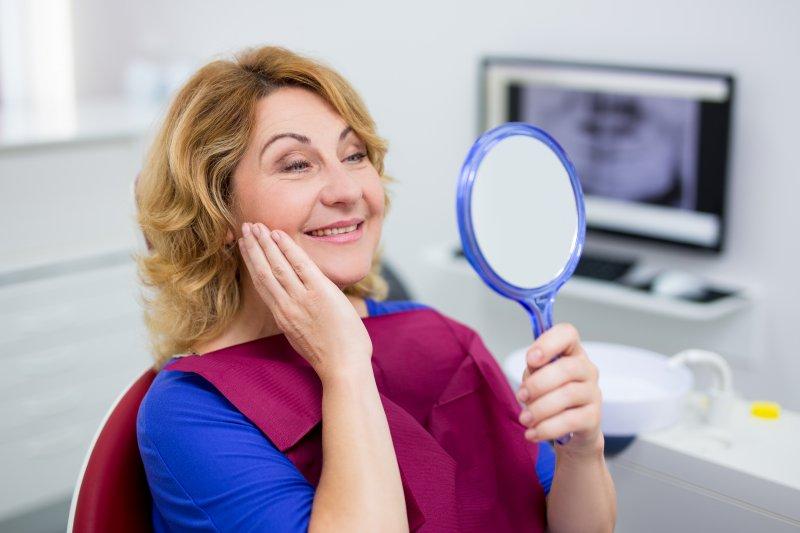 an older woman admiring her smile after a dental checkup in Burlington
