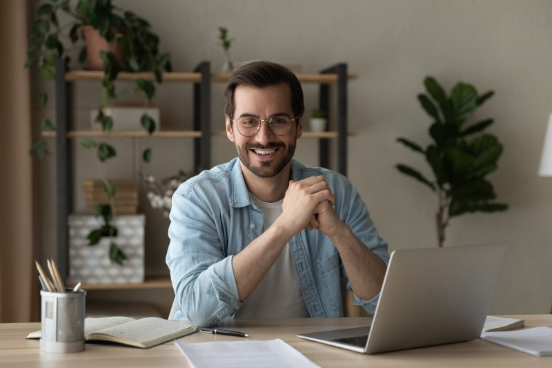 Man sitting at desk with a confident smile