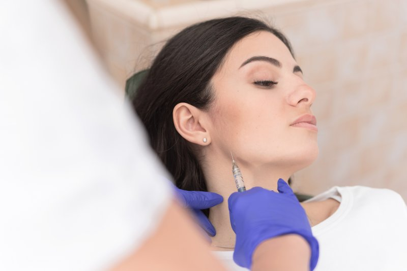 Dentist injecting BOTOX into patient's jaw