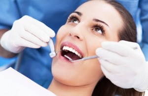 Woman visiting the dentist burlington loves to use up her benefits for 2015