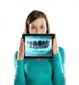Woman holding digital x-ray at emergency dentistry burlinton trusts from complete dental care